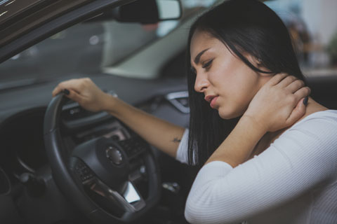 Women in car holding neck in pain